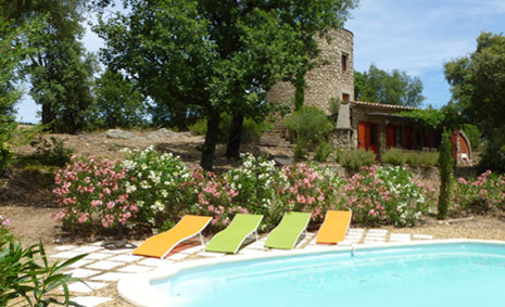 The swimming pool viewed from the garden. There are 4 brightly coloured sun loungers and the Moulin is in the background. The pool is bordered with Oleanders.